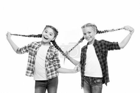Photo pour Un cheveu si long. Les petites filles heureuses portent des cheveux tressés. Mignon petit enfantin tenir des tresses de cheveux. Luxueuses extensions de cheveux. Salon de coiffure pour enfants . - image libre de droit
