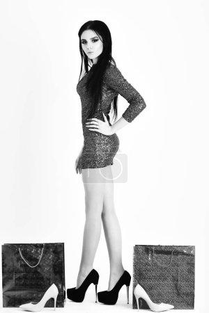 Photo pour Jolie femme ou fille mignonne sexy avec lumineux maquillage sur visage adorable avec des cheveux long brune en robe de paillettes vert avec orange et roses sacs à provisions, des colis, des chaussures isolés sur fond blanc - image libre de droit