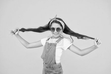 Photo pour Cheveux forts. Enfant mignon fille de la mode. Concept de mode d'été. Fille longs cheveux bouclés lunettes de soleil attaché foulard. Tendance mode. Tu peux avoir tout ce que tu veux si tu t'habilles pour ça. Petite fashionista . - image libre de droit