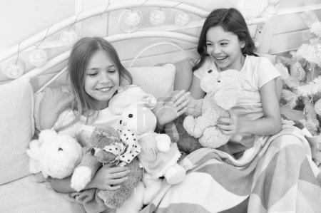 Photo pour Remplissez vos cadeaux de Noël avec joie. Petites filles jouent avec des jouets. Petits enfants profiter de Noël. Petits enfants s'amuser de Noël. Enfants heureux dans son lit à l'arbre de Noël. Jeux de l'enfance sur Noël et nouvel an. - image libre de droit