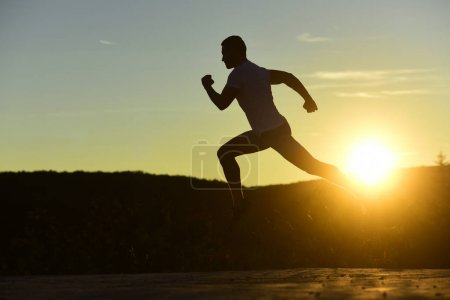 Photo for Sportsman jogging in evening catching the sun. Man with sportive figure practices sport running for life. Athlete runs on dawn sky background, copy space. Sport and training concept. - Royalty Free Image