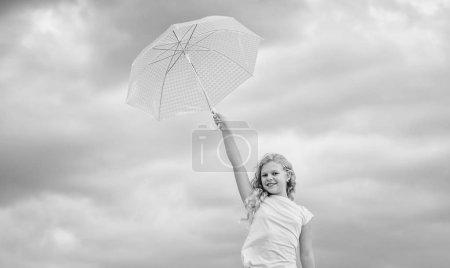Photo pour Joyeuse journée des enfants. Profiter de la facilité. Enfant insouciant à l'extérieur. Prévisions météorologiques. Prêt pour tout temps. Le temps change. De l'air frais. Fille avec fond ciel nuageux parapluie. Liberté et fraîcheur . - image libre de droit