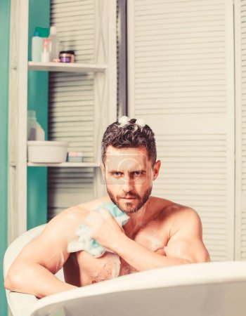 Photo pour Prendre un bain avec de la mousse de savon. Se faire plaisir avec un bain chaud. Soin et routine beauté. Homme beau mec musclé relaxant dans la baignoire. Macho avec éponge prendre bain à la maison. Concept métrosexuel . - image libre de droit