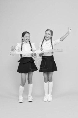 Photo pour Des élèves confiants. joyeuses petites filles étudient les mathématiques. les élèves utilisent la règle jaune. disciplines de tige. retour à l'école. Mathématiques et géométrie. Des enfants en uniforme. amitié scolaire . - image libre de droit