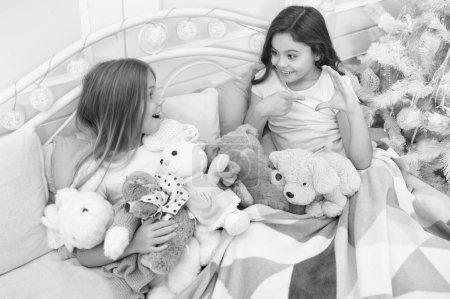 Photo pour Père Noël, s'il vous plaît arrêter ici. Petits enfants s'amuser de Noël. Petites filles jouent avec des jouets. Petits enfants profiter de Noël. Enfants heureux dans son lit à l'arbre de Noël. Jeux de l'enfance sur Noël et nouvel an. - image libre de droit