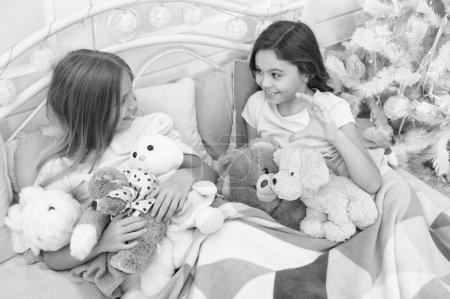 Photo pour Bon sang, sois joyeux. Les jeunes enfants apprécient Noël. Les petites filles jouent avec des jouets. Les petits enfants s'amusent à Noël. Joyeux enfants au lit au sapin de Noël. Jeux d'enfance sur Noël et la nouvelle année . - image libre de droit