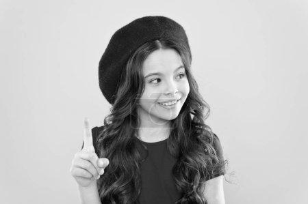 Photo pour Fille heureuse avec de longs cheveux bouclés en béret. enfance. salon de coiffure. enfant parisien sur fond jaune. mode d'été et beauté. Petite fille au chapeau à la française. excellente idée pour un nouveau style. - image libre de droit