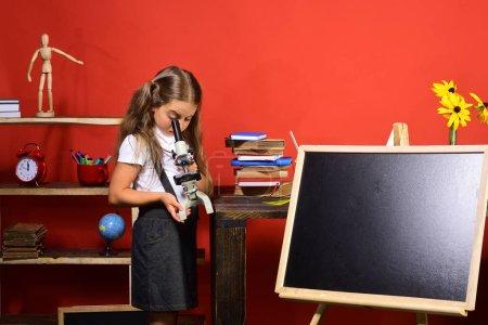 Photo pour Écolière avec visage occupé dans sa classe. Jeune fille se penche sur son microscope et se démarque par le tableau noir, espace de la copie. Concept de l'éducation et expériences. Fournitures scolaires et chevreau sur fond de mur rouge - image libre de droit