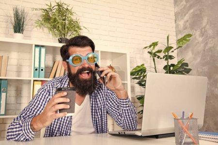 Photo pour C'est un homme funky. Homme fou travaillant occupé dans le bureau. Homme brutal avec la longue moustache et la barbe buvant le café et parlant au téléphone portable. Homme barbu dans le modèle occasionnel dans son lieu de travail. - image libre de droit