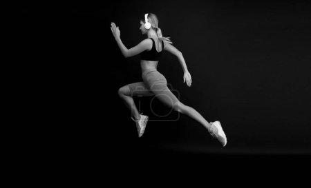 Photo pour Dur de se mettre en forme. Une femme a un fond noir. Jogger saut à long terme. Ajustez athlète dans les vêtements de sport de mode. Athlétique féminine sprinteuse ou coureuse. Actif et dynamique. Cours vite, finis bientôt . - image libre de droit