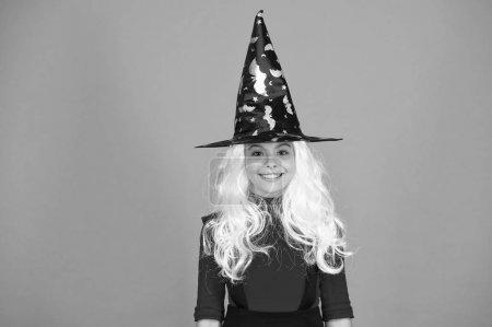 Photo pour De bonne humeur. fantasme magique. fille souriante fête d'Halloween. mystérieuse sorcière. petit chapeau de sorcière enfant. Un tour ou un régal. cheveux gris charme surnaturel. Enfant enchanteur fond orange. joyeux Halloween. - image libre de droit