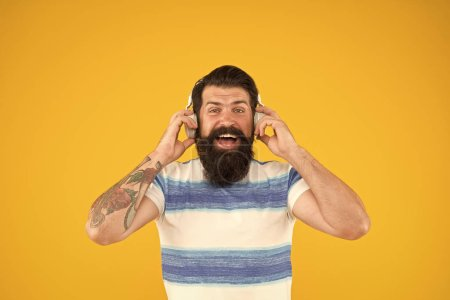 Photo pour Free time. summer music mix. Man hipster listen song yellow background. enjoy summer vacation. Melody for relax. happy bearded meloman headphones. mega hits. summer in the city. Summer playlist. - image libre de droit