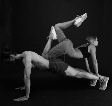 Famille sportive. Entraînement en couple. Exercices pour les muscles. Instructeur personnel au gymnase. Vêtements pour la formation d'entraînement. Sentiment de soutien. Sportsman push ups séance d'entraînement avec fille en forme sur le dos. Couple aime le sport