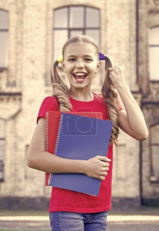 Photo for Achieving high standards. Cute little bookworm. Little girl school student. Secondary school student. School education concept. Cute smiling small child hold books educational institution background. - Royalty Free Image