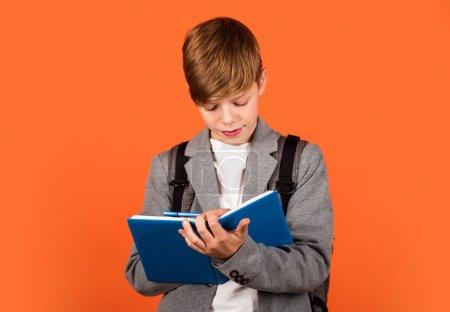Photo pour L'entraînement est parfait. Le petit enfant fait ses devoirs. Le petit garçon écrit dans son journal de devoirs et son carnet de notes. Devoir. Enseignement à domicile. Cours particulier. École et éducation. Club devoirs. - image libre de droit