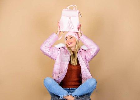 Photo pour Combinaison tendre. Accessoires assortis. Accessoire de mode. Fille adorable modèle montrant son sac à dos en cuir fantaisie. Le sac à dos est tout ce dont vous avez besoin. Petit sac à dos et chapeau tricoté. Tenue pastel totale. - image libre de droit