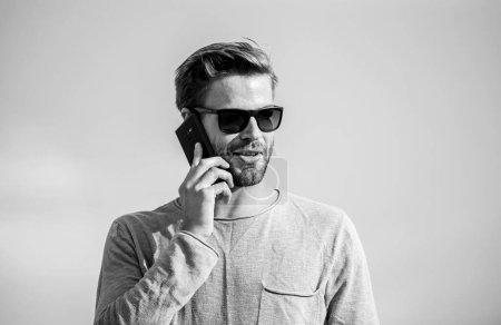Application et internet. Hipster porter des lunettes de soleil tenir téléphone mobile fond ciel. Appel du smartphone Hipster. Importante conversation mobile. Un appel mobile. Restez en contact. Concept d'appel mobile