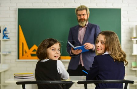 Photo pour Teacher and pupils working at desk together at the elementary school. disclose and develop creativity. Teacher working with Creative Kids. small girls children at school. back to school. - image libre de droit