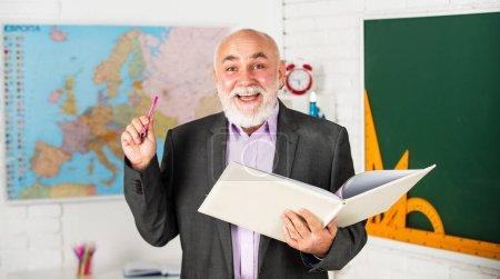 Photo pour Créer un environnement d'étude libre de distraction. enseignement des mathématiques à l'école. barbu homme donne des marques. écrire des notes dans le livre. heureux maître de conférences prendre des notes. salle de classe avec carte et tableau. retour à l'école. - image libre de droit