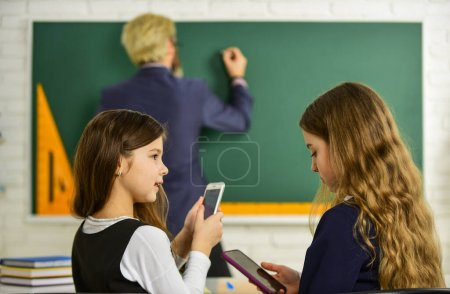 Photo pour Concentrated on studying. Students Studying And Reading. homework writing and reading. children girls and teacher man. Elementary School Teacher Giving Support In Classroom. Pupil Wearing Uniform. - image libre de droit