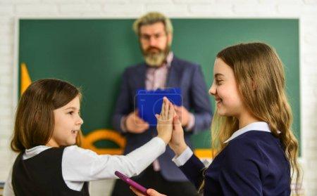 Photo pour Avoir du plaisir. les petites filles à l'école. retourner aux études. Enseignant et élèves travaillant au bureau ensemble à l'école élémentaire. divulguer et développer la créativité. Enseignant travaillant avec Creative Kids. - image libre de droit