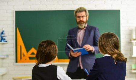 """Photo pour Enseignant de l """"école primaire offrant du soutien en classe. Le port de l'uniforme des élèves. Petits élèves étudiant et lisant. faire ses devoirs de rédaction et de lecture. Les filles et l'enseignant. - image libre de droit"""