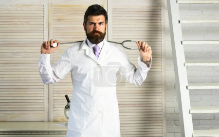 Photo for Man in surgical uniform with stethoscope on neck on wooden background. Healthcare and treatment concept. Physician with serious face ready to diagnose. Doctor in white medical coat holds equipment - Royalty Free Image