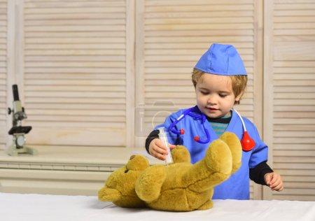 Photo for Boy in surgical uniform holds syringe on wooden background. Kid in doctor coat makes injection to teddy bear. Medical education and childhood concept. Child with interested face playing doctor - Royalty Free Image
