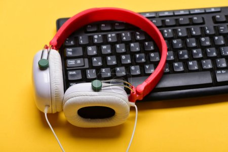 Photo for Music and digital equipment concept. Sound recording idea. Earphones in red and white colors with computer keyboard. Electronic appliances on light orange background. Headphones and black keyboard - Royalty Free Image