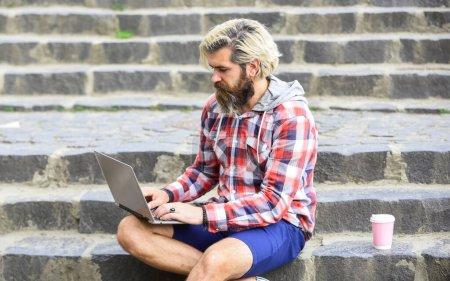Photo pour Homme à la pige travaillant sur ordinateur. Homme d'affaires utilisant un carnet de notes. emporter le café. Évasion de fonctions. entrepreneurs prospères. Homme mûr assis dans un escalier muni d'un ordinateur portable et vérifiant son courriel. - image libre de droit