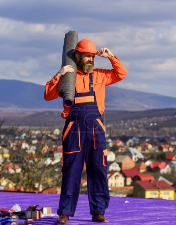 Photo for Flat roof installation. Man hard hat working outdoor landscape background. Building house. Install vapor barriers or layers of insulation on flat roofs. Roofer constructing roof. Master repair roof. - Royalty Free Image