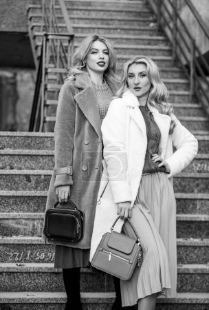 Photo for Glamour models look luxuriously. sexy blong women. autumn season. modern life. european winter. girls warm coat on stairs. faux fur coat fashion. stylish business ladies leather bag. - Royalty Free Image