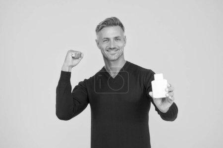 Photo pour Ça sent bon toute la journée. Un gars heureux tient une bouteille d'eau de Cologne. L'hygiène personnelle. Beau homme présentant des produits d'hygiène. Lotion et lavage de corps. Hygiène quotidienne et santé. Habitudes d'hygiène puissantes, espace de copie . - image libre de droit