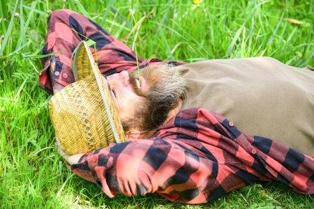Photo pour Saison d'été en parfait état. brutal ranch hipster porter chemise à carreaux. agriculture et agriculture. agriculteur détendu en chapeau de paille. homme mûr jardinier se détendre sur l'herbe verte. profiter du printemps nature. - image libre de droit
