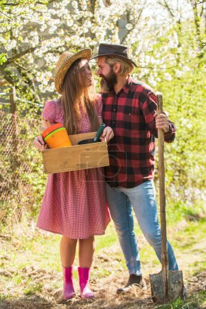 Organic farm. Smiling couple in love gardening. Girl hold box with pots and tools. Soils and fertilizers. Planting plants. Family farm. Farming season. Happy couple ranch owners. Ecology environment