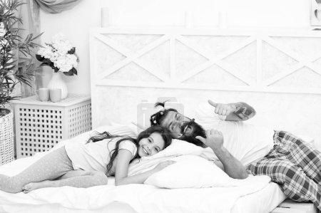 Photo pour Bonne nuit au matin. Bonne famille aller dormir la nuit. Un barbu a endormi sa fille. Au lit. Soirée ou nuit. Fais de beaux rêves. Dormir toute la nuit. La vie est meilleure en pyjama . - image libre de droit