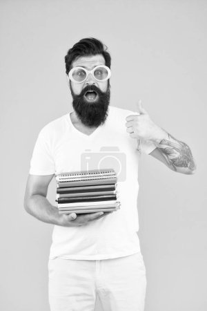 Photo for Stationery admirer. Buy sketchbooks. Hipster eccentric guy hold pile notepads. Stationery shop. Study hard. Language courses. Buy stationery. Diverse assortment office supplies. Colorful stationery. - Royalty Free Image