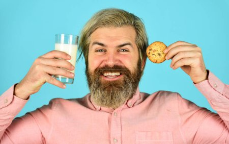 Photo for Bearded man drink milk with cookies. Leave it for Santa. Breakfast or lunch. Milk and sweet cookies. Happy hipster eat cookie dessert. Delicious treats. Homemade is best. Recipe for baking cookies. - Royalty Free Image