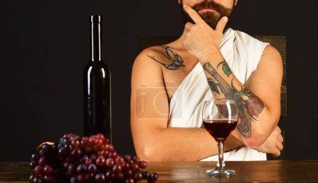 Gott des Weins sitzt bei Weinflasche und dunklen Trauben.