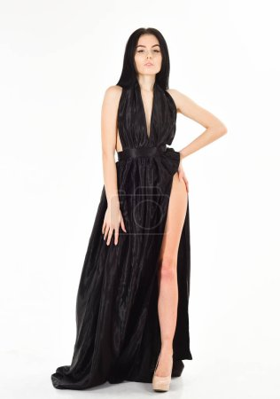 Photo pour Lady, sexy fille en robe. Une jeune fille séduisante porte une robe de soirée chère à la mode avec une fente érotique. Concept de robe de mode. Femme en élégante robe de soirée noire avec décollete, fond blanc - image libre de droit