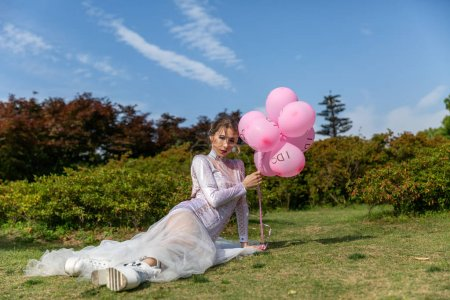 Photo for Young woman in white dress holding balloons - Royalty Free Image