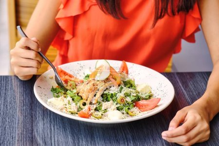 Photo for Closeup to dish of salad eaten by young woman with a fork - Royalty Free Image