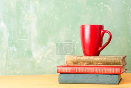 Books and a red cup on the table