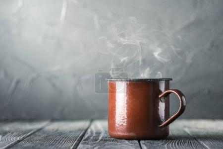 Brown mug of hot tea on table