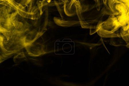 Photo pour Fumée jaune sur fond noir - image libre de droit