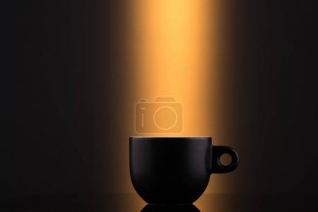 Black cup on an orange background