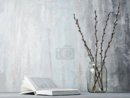 Book and willow branches on table, close up...