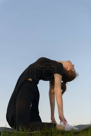 Girl in black clothes practicing yoga against the blue sky