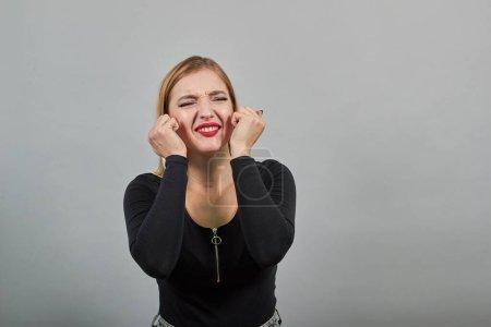 Joven chica rubia en chaqueta negra mujer irritada que sufre de dolor en los oídos