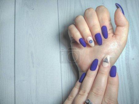 Photo pour Manucure féminine sur de longs ongles ronds. Gel vernis à ongles couleur bleu mat avec un motif de camouflage de l'œil dans le triangle. Finition mate bleue avec un design de la planète et le symbole maçonnique . - image libre de droit
